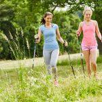 Zwei junge Frauen zusammen beim Nordic Walking im Sommer